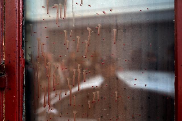 Na snímke stopy po krvi na okne kaviarne Carillon