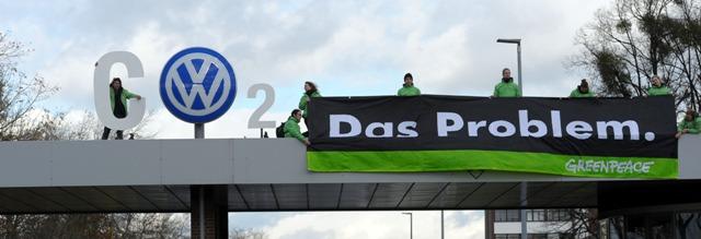 """Na snímke aktivisti Greenpeace stoja pri nápise CO2, do ktorého zakomponovali logo nemeckej automobilky Volkswagen a transparente s nápisom """"Problém"""" pri závode automobilky v nemeckom meste Wolfsburg"""
