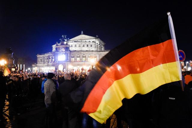 Demonštrant drží nemeckú vlajku počas demonštrácie skupiny PEGIDA proti islamizácii Západu v Drážďanoch