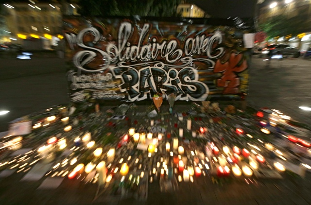 """Poukladané zapálené sviečky pod nápisom """"Solidarita s Parížom"""" na znak úcty k mŕtvym, ktorí prišli o život počas piatkových teroristických útokov"""