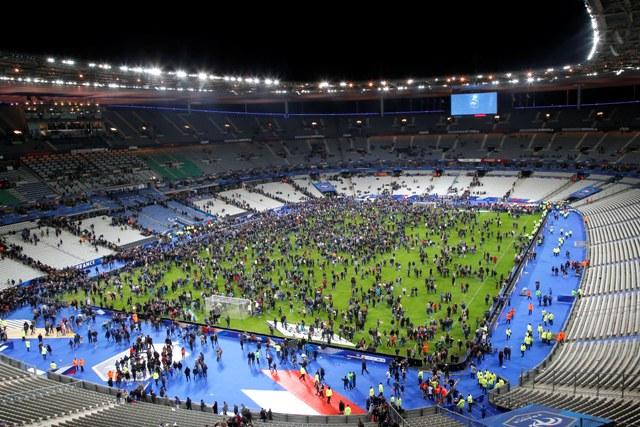 Diváci utekajú na trávnik národného štadióna Stade de France  po priateľskom futbalovom zápase medzi Francúzskom a Nemeckom 13. novembra 2015 v Paríži