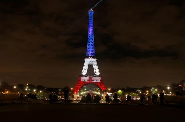 Ľudia sa pozerajú na Eiffelovu vežu, ktorá je osvetlená francúzskymi národnými farbami na znak úcty k mŕtvym, ktorí prišli o život počas piatkových teroristických útokov