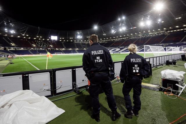 Policajti hliadkujú pri hracej ploche futbalového štadióna v Hannoveri, ktorý museli evakuovať pred začiatkom  priateľského zápasu Nemecko - Holandsko z dôvodu hrozby bombovým atentátom