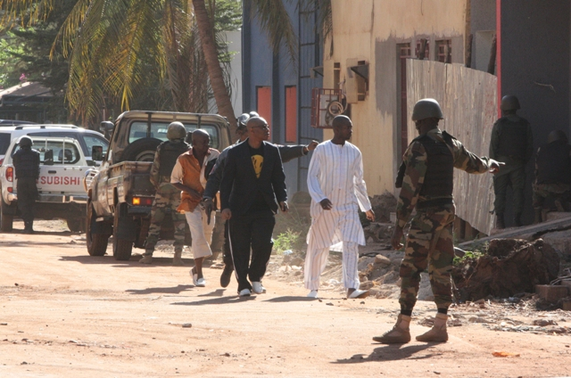 Na snímke bezpečnostné jednotky eskortujú ľudí, ktorí utiekli z hotela Radisson Blu v malijskom meste Bamako