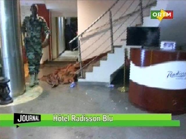 Na videosnímke člen bezpečnostných jednotiek kráča okolo zakrytého tela v hoteli Radisson Blu v malijskom meste Bamako