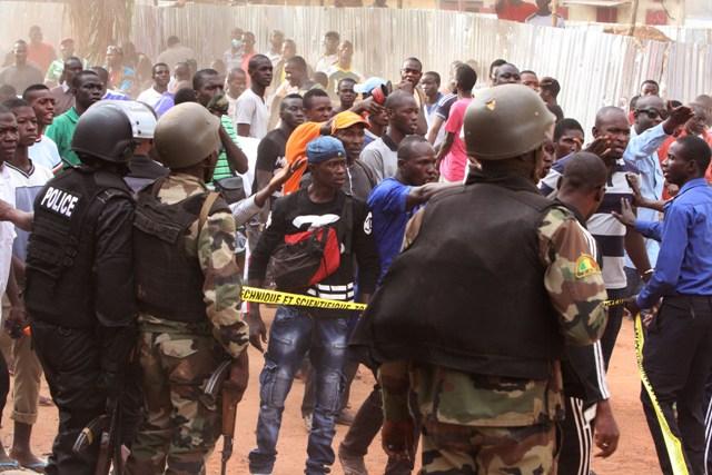 Snímka z 20. novembra 2015, kde malijskí vojaci sa pokúšajú kontrolovať dav zvedavcov pri hoteli Radisson Blu v malijskom meste Bamako