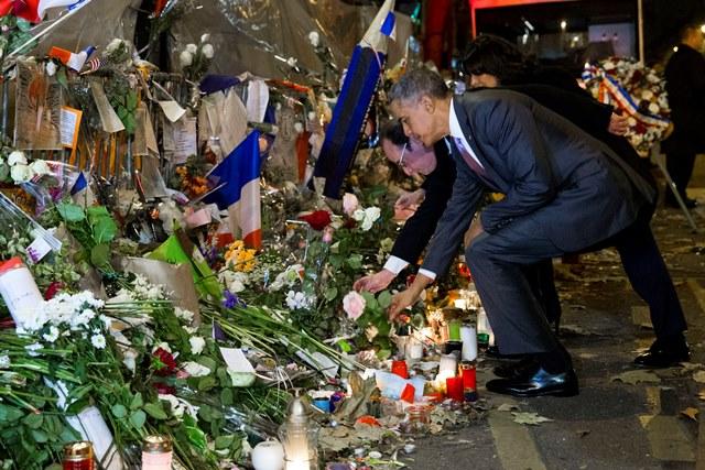 Na snímke americký prezident pokladá kvetinu pri provizórnom pamätníku obetiam útokov spolu s prezidentom Francoisom Hollandom a starostkou Paríža