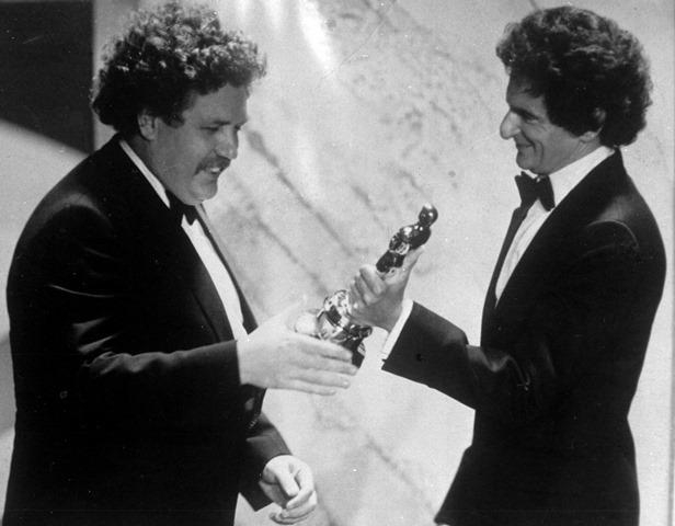 Na archívnej snímke z 29. marca 1982 britský herec a scénarista Colin Welland (vľavo) si preberá Oscara za najlepší scenár od Jerzyho Kosinského počas 54. ročníka  udeľovania cien Americkej filmovej akadémie v Los Angeles