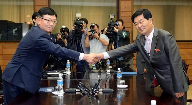 Na snímke z roku 2013 šéf juhokórejskej vysokopostavenej pracovnej delegácie Suh Ho (vľavo) si podáva ruku so svojím severokórejským partnerom Park Chol-Suom