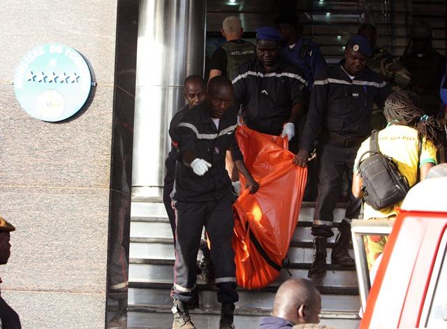Na snímke príslušníci bezpečnostných síl vynášajú mŕtve telo z hotela Radisson Blu