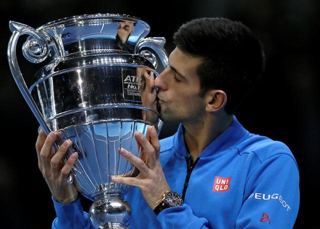 Na snímke srbský tenista Novak Djokovič bozkáva víťaznú trofej mužskej svetovej jednotky po víťazstve nad Japoncom Keiom Nišikorim v skupine Stana Smitha na Turnaji majstrov v Londýne