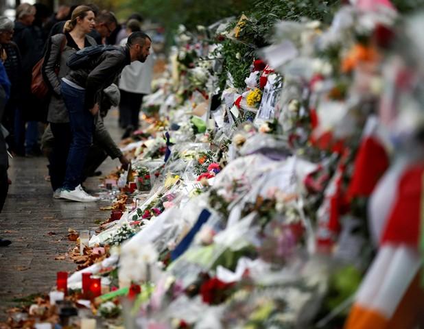Na snímke ľudia sa pozerajú na kvety a odkazy položené pred koncertnou halou Bataclan v Paríži
