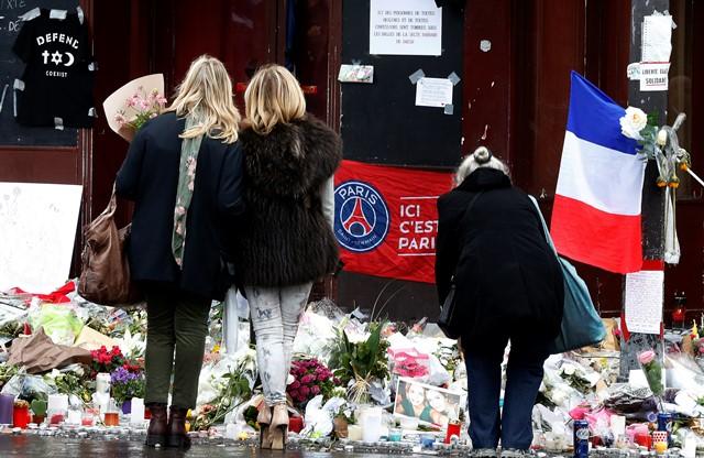 Na snímke ľudia sa pozerajú na kvety a sviečky položené pred reštauráciou Le Carillon v Paríži