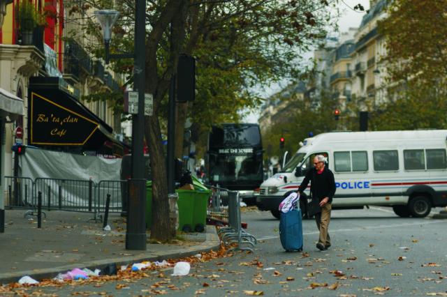 Na snímke muž prechádza pri uzatvorenej ulici pri divadle Bataclan po piatkových teroristických útokoch v Paríži