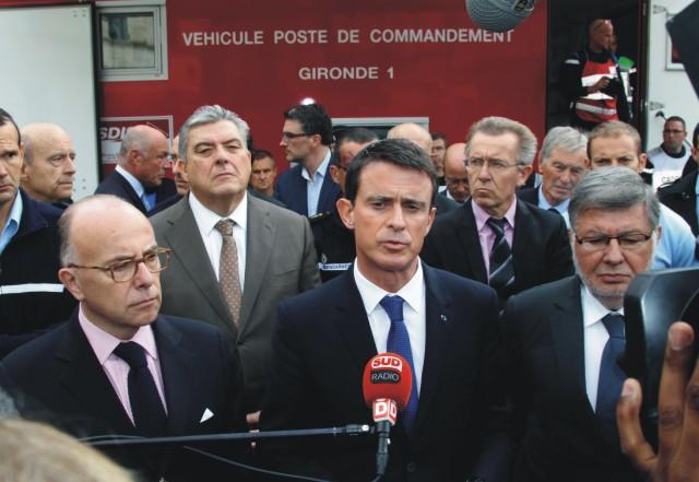 Francúzsky premiér Manuel Valls (uprostred) a minister vnútra Bernard Cazeneuve (vľavo)