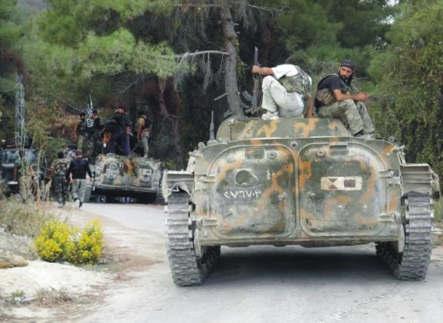 Na archívnej snímke príslušníci Slobodnej sýrskej armády sedia sediaci na obrnenom vozidle