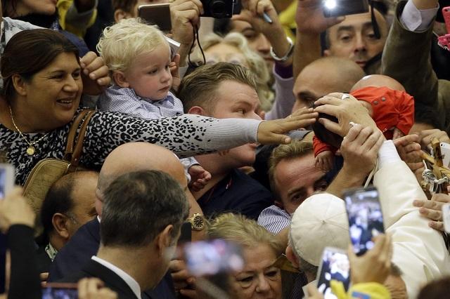 Pápež František sa zdraví s príslušníkmi etnických skupín Sinti a Rómov a ďalšími kočovnými skupinami počas príchodu na audienciu vo Vatikáne 26. októbra 2015