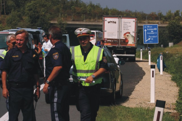 Na archívnej snímke stoja policajti pred nákladným autom s logom slovenskej spoločnosti Hyza, ktoré stojí odstavené na diaľnici A4 neďaleko Parndorfu 27. augusta 2015. V nákladnom priestore auta našli rakúski policajti 71 tiel utečencov