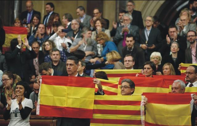 Regionálny parlament autonómneho spoločenstva Katalánsko na severovýchodne Španielska hlasoval v pondelok 9. novembra 2015 za rezolúciu o odtrhnutí od Španielska. Otvorila sa tým cestovná mapa k nezávislosti, ktorú centrálna vláda v Madride mieni zablokovať. Na snímke poslanci regionálneho parlamentu autonómneho spoločenstva Katalánsko držia španielsku a katalánsku vlajku po skončení zasadnutia parlamentu v Barcelone 9. novembra 2015