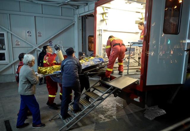 Na snímke záchranári nakladajú do sanitky zranenú osobu po požiari, ktorý vypukol v nočnom klube Colectiv