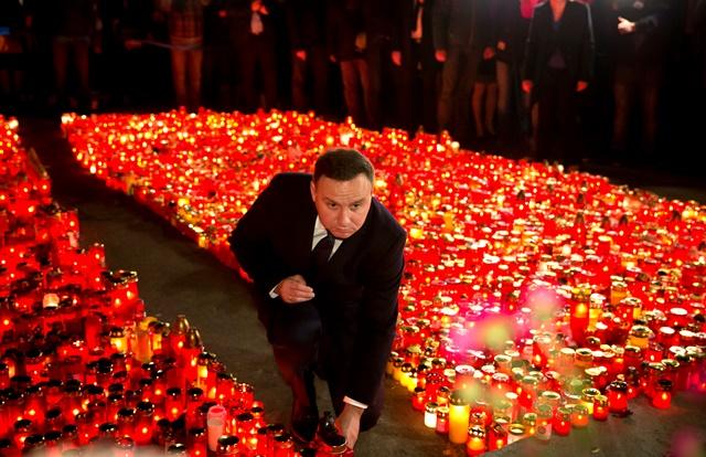 Na snímke  poľský prezident Andrej Duda zapaľuje sviečku na pamiatku obetí piatkového požiaru pred nočným klubom Colectiv v Bukurešti