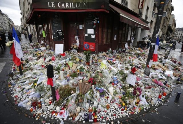 Kvety a sviečky položené pred reštauráciou Le Carillon v Paríži 19. novembra 2015 na pamiatku obetí útokov