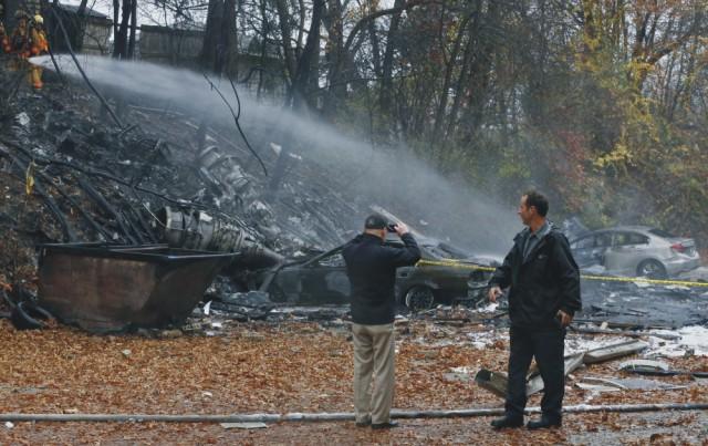 Na snímke zbytky po páde lietadla, ktorého požiar uhasujú po páde hasiči