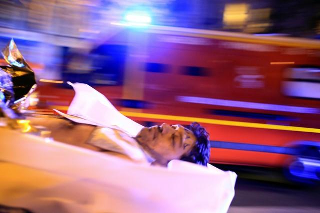 Na snímke muž počas evakuácie po streľbe z koncertnej siene  Bataclan