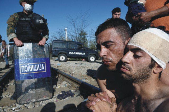 Na snímke migranti sediaci na koľajniciach. Marockí, iránski a pakistanskí migranti zablokovali dnes železničnú dopravu na severogréckej hranici s Macedónskom s požiadavkou, aby im bolo umožnené odísť do západnej Európy