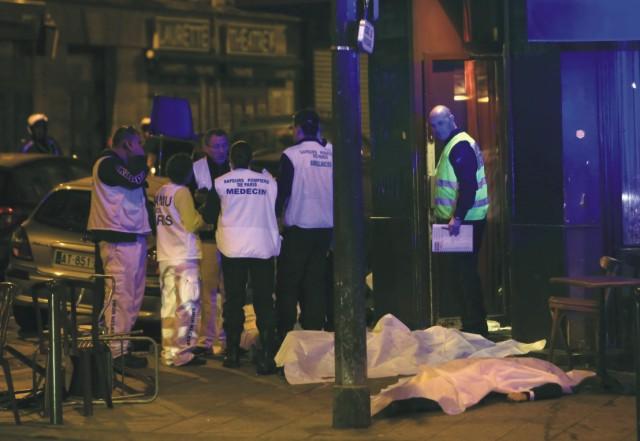 Zdravotníci stoja vedľa obetí pred reštauráciou 13. novembra 2015 v Paríži. K teroristickému útoku v Paríži v blízkosti Námestia republiky, na hranici 10. a 11. obvodu francúzskej metropoly, došlo v piatok večer približne o 23.00 h