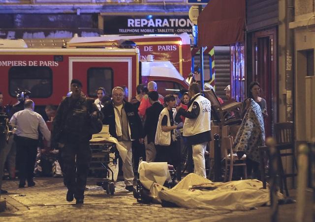 Na snímke policajti a hasiči sa zhromažďujú okolo tela obete v 10. obvode francúzskej metropoly Paríž