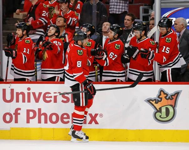 Slovenský hráč Chicago Blackhawks  Marián Hossa oslavuje so spoluhráčmi gól do bránky Winnipegu Jets v hokejovom zápase zámorskej NHL
