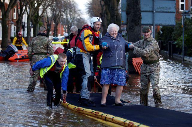Vojaci a záchranári evakuujú staršiu ženu počas záplav v Carlisle na severozápade Anglicka
