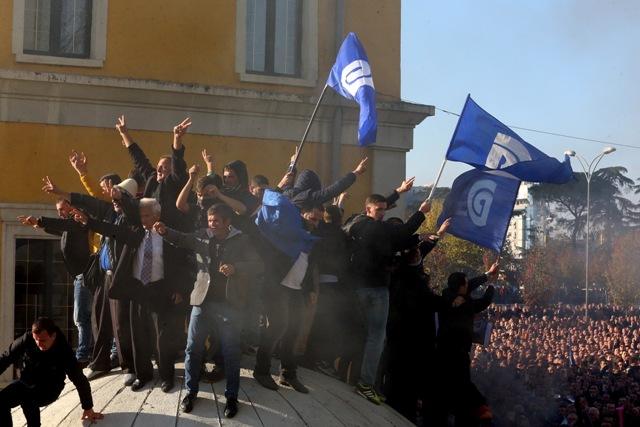 Stúpenci albánskej opozície stoja na bunkri počas protestu v Tirane