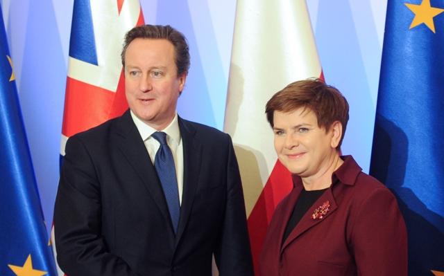 Britský premiér David Cameron (vľavo) si podáva ruku s poľskou premiérkou Beatou Szydlovou pred ich stretnutím vo Varšave