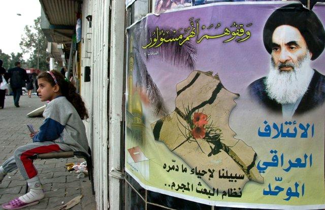 Na ilustračnej snímke iracké dievča sedí vedľa volebného plagátu šítskeho klerika Ali al-Sistáního