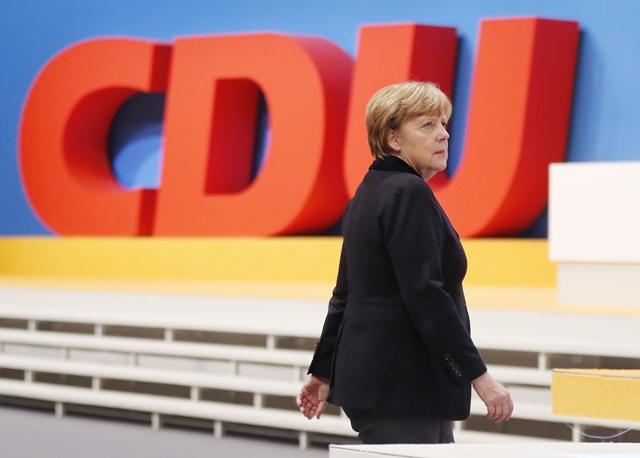 Na snímke šéfka Kresťanskodemokratickej únie (CDU) a nemecká kancelárka Angela Merkelová kráča okolo loga strany na spolkovom zjazde CDU v Karlsruhe