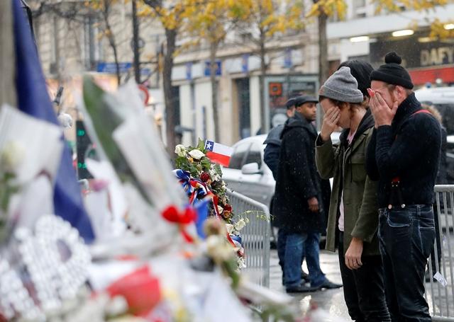 Na snímke členovia americkej rockovej skupiny Eagles of Death Metal Jesse Huges (vpravo) a Julian Dorio (vľavo) vzdávajú 8. decembra 2015 pred klubom Bataclan v Paríži hold 89 obetiam, ktoré zahynuli počas teroristického útoku v klube Bataclan pri ich koncerte 13. novembra 2015