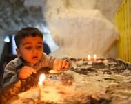 Chlapec v tábore Mar Ellia v Erbile zapaľuje sviečku v Jaskyni svätej Rodiny