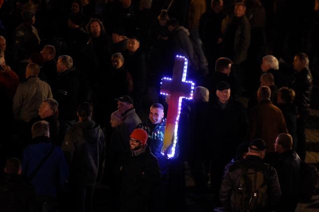 Na snímke demonštrant drží osvetlený kríž v nemeckých národných farbách počas demonštrácie skupiny PEGIDA