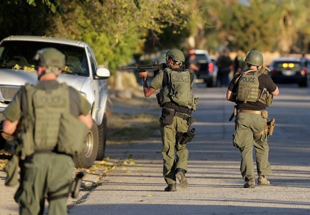 Na snímke policajti pátrajú po strelcovi