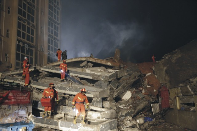Záchranári hľadajú ľudí medzi ruinami budov, ktoré sa zrútili v dôsledku zosuvu pôdy v Šen-čene v juhočínskej provincii Kuang-tung 20. decembra 2015. Rozsiahly zosuv pôdy v priemyselnej zóne juhočínskeho mesta Šen-čen zavalil takmer 20 budov