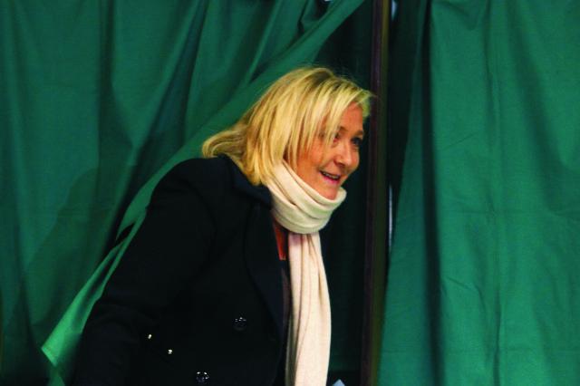 Na archívnej snímke líderka Národného frontu Marine Le Penová vychádza spoza plenty v prvom kole regionálnych volieb vo Francúzsku vo francúzskom Henin Beaumonte 6. decembra 2015