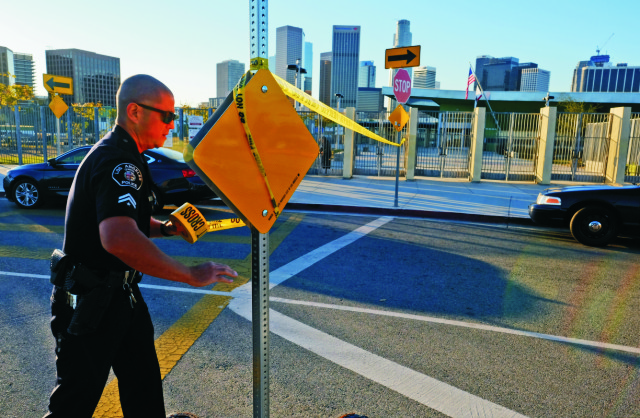Policajt dáva žltú policajnú pásku a uzatvára vstup do školy Edward Roybal High School v Los Angeles 15. decembra 2015. Los Angeles uzatvorilo všetky školy v meste kvôli hrozbe bombového útoku