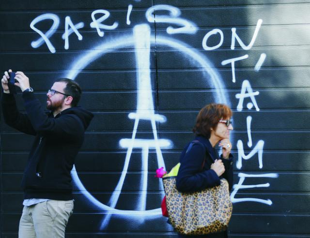 Na archívnej snímke ľudia kráčajú okolo kresby na garáži oproti reštaurácie  Rue de Charonne, kde sa v odohral teroristický útok