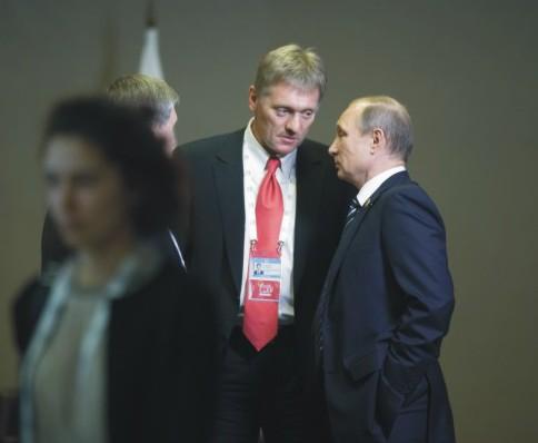 Na snímke v pozadí vľavo Dmitrij Peskov a Vladimir Putin