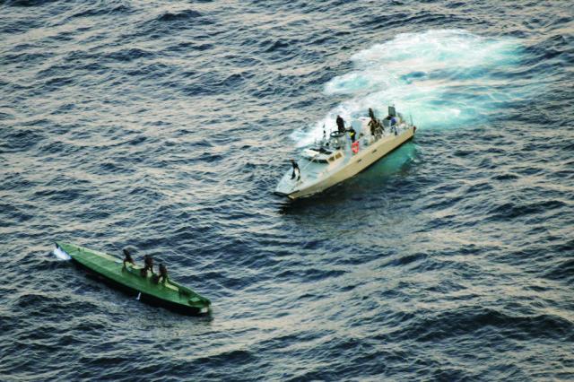 Na snímke členovia námornej pobrežnej hliadky plávajú smerom k zadržanej pašeráckej ponorke s drogovým kontrabandom po tom, ako ju odtiahli