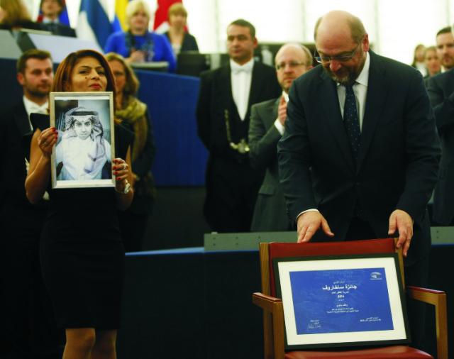 Ensaf Hajdarová (vľavo), manželka väzneného saudskoarabského blogera Ráifa Badawího ukazuje portrét svojho manžela po tom, čo si za ňho prevzala Sacharovovu cenu 16. decembra 2015 v Štrasburgu. Cenu v jeho mene z rúk predsedu EP Martina Schulza (vpravo) prevzala Badawího manželka Ensaf Hajdarová
