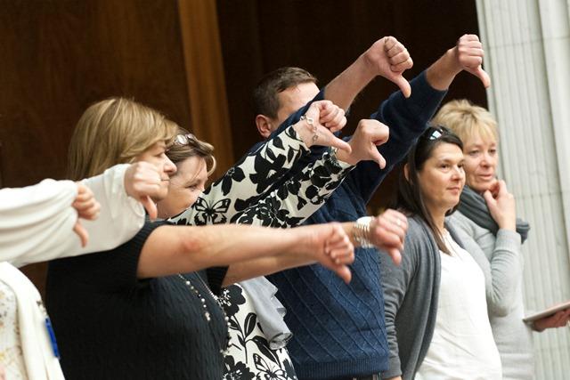Na snímke zdravotníci  ukazujú palce nadol po hlasovaní v parlamente, keď poslanci prelomili veto a opäť odobrili zákon upravujúci platy zdravotníkov