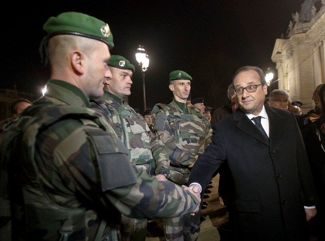 Francúzsky prezident Francois Hollande (vpravo) podáva ruku zahraničnému legionárovi počas kontroly bezpečnostných opatrení na Avenue des Champs-Élysées v Paríži